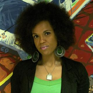 A black woman with afro and large green earrings in front of a colorful wall.