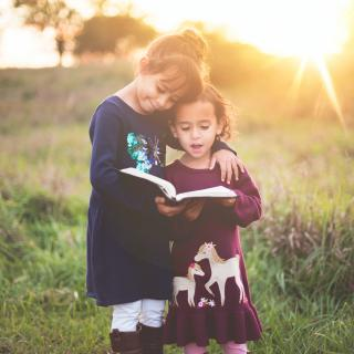 two children stand together in a field holding a book