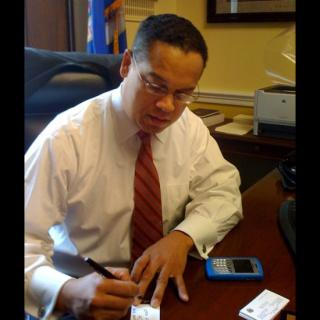 Rep. Keith Ellison of Minnesota, writing at his desk.