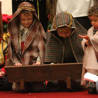 Small children, in costume, lean over a manger during a church Christmas pageant
