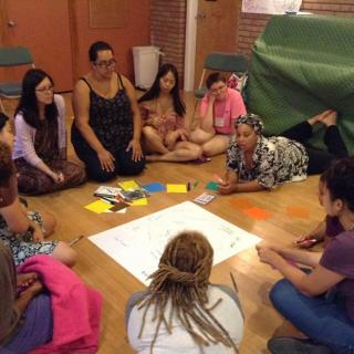 a group of women of color sit around a piece of chart paper