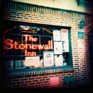 "A photo of a brick storefront with ""The Stonewall Inn"" in neon letters in the window."