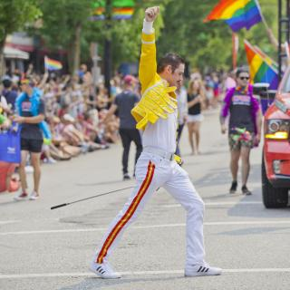 In the middle of a Pride parade, rainbow flags in the background, a Freddie Mercury impersonator strikes a powerful pose.