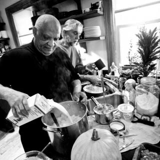 In a black and white photo, someone pours milk into a large pot of mashed potatos. Behind him, someone else prepares food at a kitchen counter.