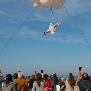 Above a crowd of people looking up and taking pictures with their phones, a white-tutu-wearing trapeze artist is suspended from a cloud of white balloons (part of the Molecole show)..