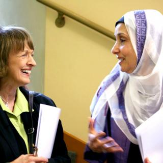 Two women, one Unitarian Universalist and one Muslim, smile at each other.