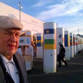 Ahti Tolvanen stands in front of pillars displaying the flags of many countries at COP21 climate conference