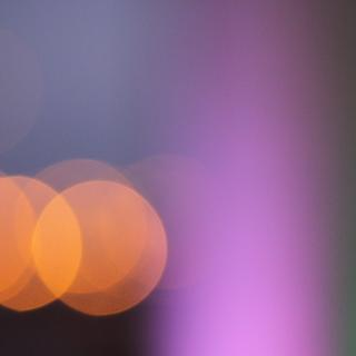 An abstract pattern of lights: orange circles next to a violet and green vertical band