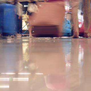 The feet and rolling suitcases of travelers are both seen, and reflected in a shiny airport floor.
