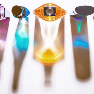 Five glass perfume bottles, photographed from above, with the colored reflections of their different sizes and shapes.
