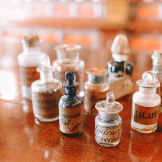 On a wooden surface, tiny antique bottles -- as if herbs or chemicals -- with labels in calligraphy.