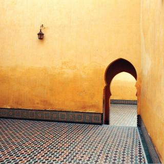Against a stark gold wall, with ornate floor tiles, a curving doorway leads into the next room.