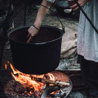 A person's arm is seen stirring the contents of a large iron cauldron, suspended over a lively fire.