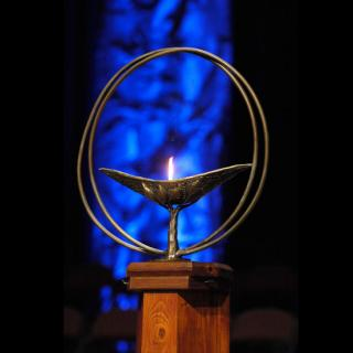 Photo of a lit chalice against a blue background