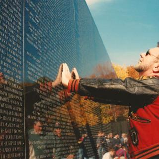 At the Vietnam Memorial Wall in Washington, a man places both hands on the wall and looks up to read names