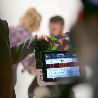 Two people on a set, obscured in the background, while a third person holds a production clapperboard with digitial numbers.