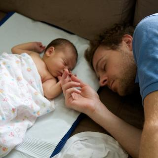 Sleeping baby and napping dad hold hands