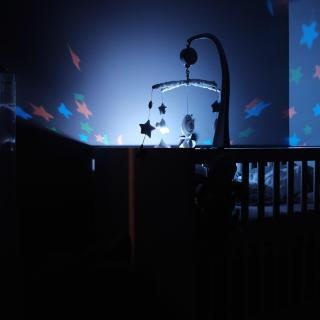 In a dark room, a lighted mobile over a baby's crib throws colored stars of light onto the walls.