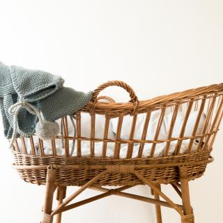 A wicker bassinet, lined with bedding, with infant clothing draped on the edge.
