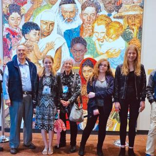 A contingent of youth and adults from First Parish Bedford UU stand in front of artwork at the United Nations