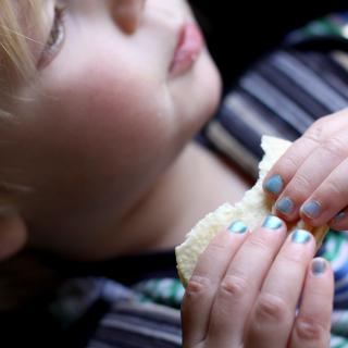 A young boy eating a cookie, wearing blue nail polish.