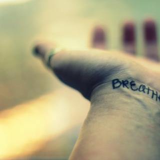 "An open hand stretches out, the word ""breathe"" written or tattooed on the wrist"