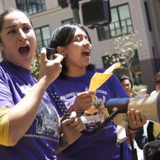 Two Latinx women from Mujeres Unidas y Activas shout to a crowd using a bullhorn.