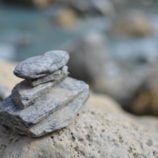 A small stone cairn with a blurry ocean in the background.
