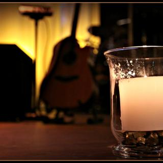 An ivory pillar candle in a clear hurrican holder, with blurred musical instruments in the background.