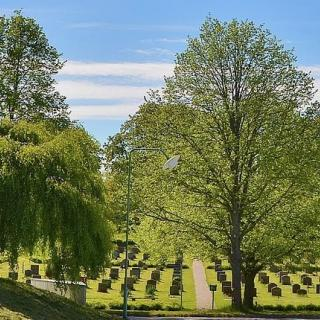 A cemetery in springtime with green grass, blue sky, and green trees.