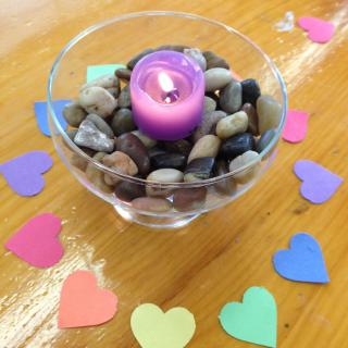 Pink candle chalice surrounded by colorful paper hearts on wooden table.
