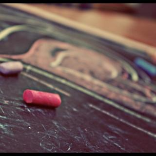 Two pieces of colored chalk, lying on a flat chalkboard, with a multi-colored heart drawn on it.