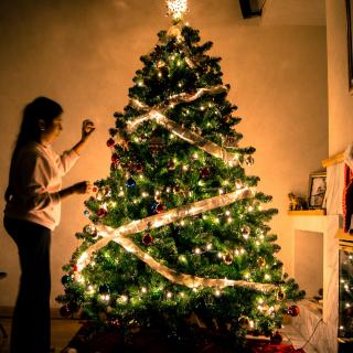 A child stands, putting the final touches on a lit Christmas tree in a dark room.