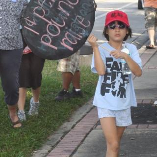 A child wearing shorts and a hat carries a sign amid adults at a protest