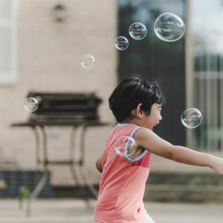 A small child, seen in profile with a huge smile on their face, runs through soap bubbles in a back yard.