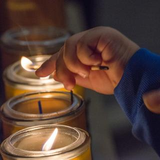 Child's_hand_lighting_votive_candle