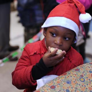 A young child eats a cookied, wearing a Santa hat, while peering at someone off-camera.