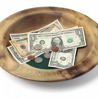 A church offering plate with money inside.