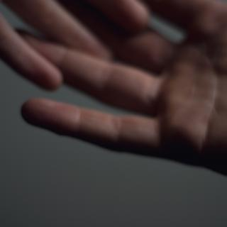 a pair of hands, only one entirely in the frame, with fingers loosely interlaced