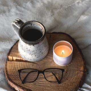 A mug of coffee, lit candle, and pair of glasses rests on a tray made of a slice of log.