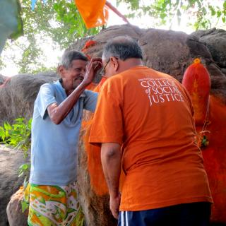 UUCSJ co-leader Mahesh Upadhyaya receives a blessing from the priest at the ancient sacred site we visited near Usgaon.