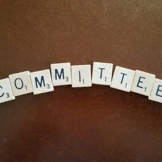 The word committee spelled out in Scrabble tiles