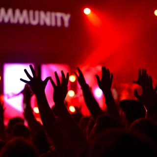 In a gathering lit by red lights, the word COMMUNITY appears on the wall as many arms wave in the air.