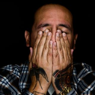 A man with tattooed hands, from the shoulders up, covers his eyes with his hand as if wiping away tears.