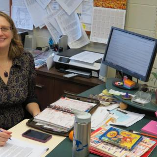 Diane Melvin, Credentialed Religious Educator, at desk