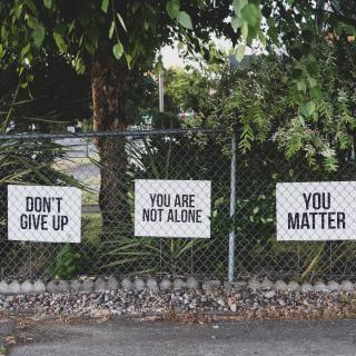 "A wire fence on an abandoned street. On the fence 3 signs are posted. They say: ""Don't give up,"" ""You are not alone,"" and ""You matter."""
