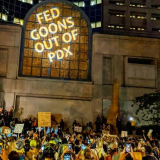 "Image of crowd of protesters in Portland, OR, where the words ""Fed goons out of PDX"" are projected on wall"