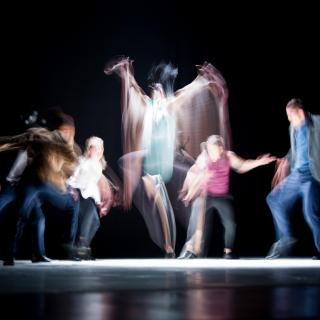 A group of dancers, lit from above, blurred by being caught in motion.