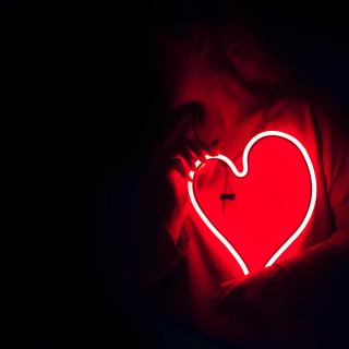 A person, seen only from the waist up in the dark, holds a red neon heart in their hands.