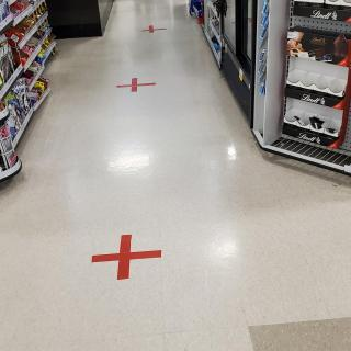 A series of large red plus signs, made out of tape, on the floor of a grocery store aisle